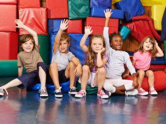 Glückliche Kinder heben Hände in der Turnhalle