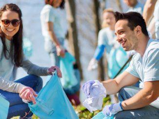Menschen sammeln Müll in blaue Müllsäcke