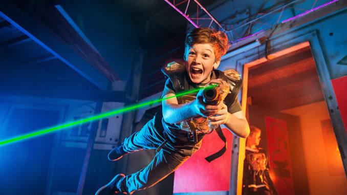 Kind im Sprung mit Laserpistole